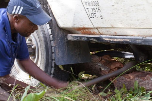 Gently removing a small piece of wood from under the front axle; Cuidadosamente removendo um pequeno pedaço de madeira debaixo do eixo dianteiro.