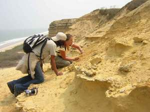 Angolan student, foreground, gets hands-on training from a PaleoAngola project team member.